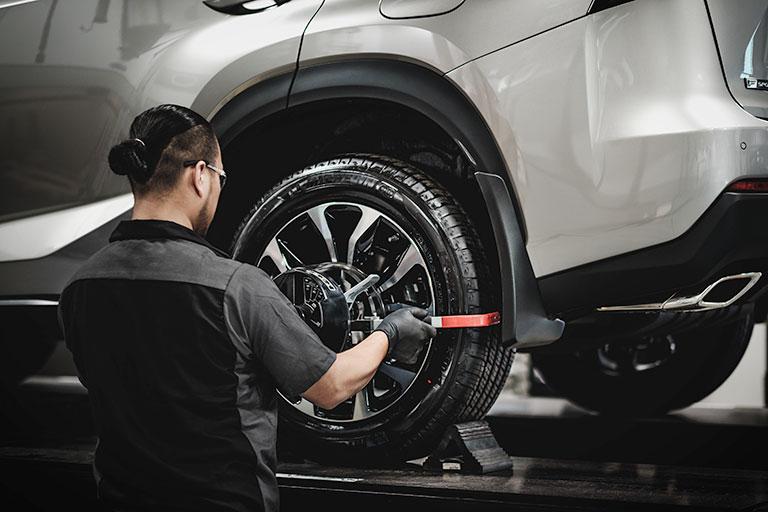 Lexus mechanic conducting s tire alignment inspection