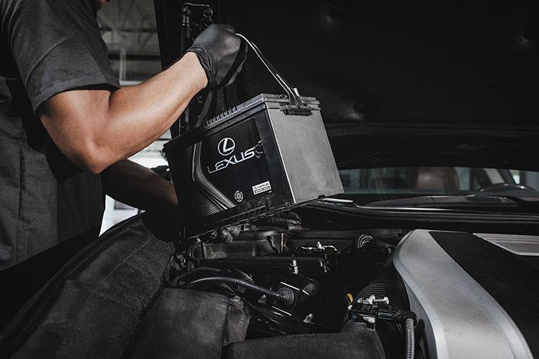 Lexus mechanic putting a premium battery into car