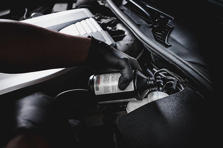 Lexus mechanic pouring genuine brake fluid into car