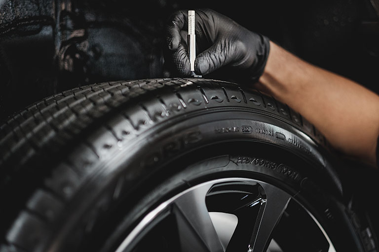 Lexus mechanic using a  tread depth gauge to measure tire tread