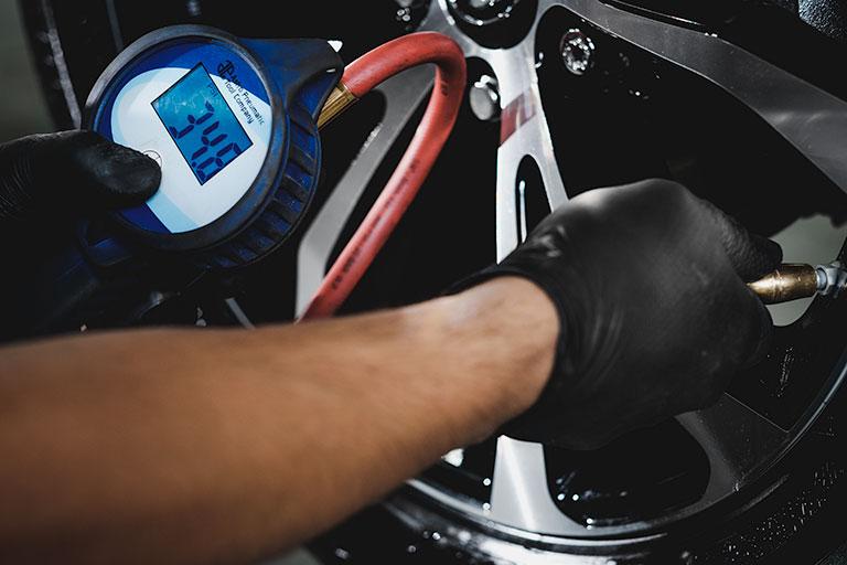 Lexus mechanic checking tire pressure