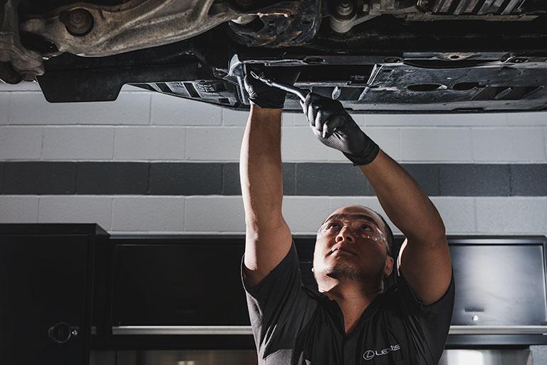 Lexus mechanic changing oil filter under raised car